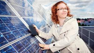 Proffessor Hele Savin står lutand mot solpanel.