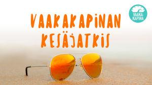 Kuvassa on oranssilinssiset aurinkolasit rannalla. Kuvassa on teksti Vaakakapinan kesäjatkis.