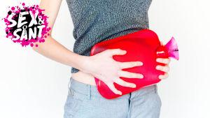 en flicka som håller en varmt vatten påse på sin mage