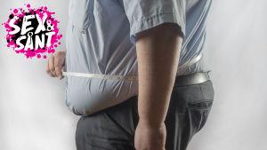en överviktig man som står mot en vit bakgrund med ett mottband runt hans midja