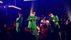 Humorgruppen KAJ står på scen iklädda gröna kavajer.