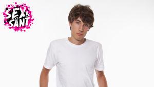 en pojke i vit t-skjorta mot en vit bakgrund som står och ser olrolig och ledsen ut