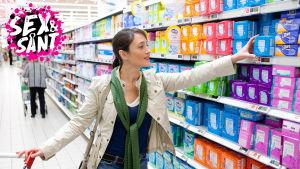 en vuxen kvinna som är i butiken och tar bindor från hyllan