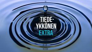 Tiedeykkönen Extra mainoskuva. Vesipisara tippuu veteen, Tiedeykkönen Extra-teksti.