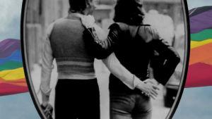 Pariskunta käsi kädessä ja sateenkaarilippu