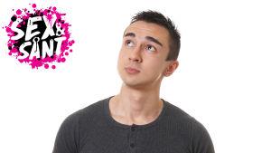 en ung man mät en vit bakgrund som står och tittar fundersamt snett uppåt