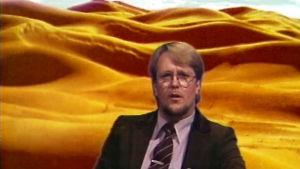 Heikki Harma juontaa Tuubi-ohjelmaa, taustakuvana hiekkaerämaa.