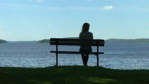 nainen istuu penkillä järven rannalla