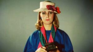 Lierihattuinen tv-kuuluttaja Riika SIllanpää pitelee kaukosäädintä kädessään väri-tv-tietoiskussa.