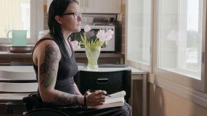 Tuhkimotarinoiden Ulla kotona pyörätuolissa, katsoo ikkunasta