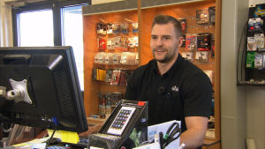 manlig försäljare bakom disken i elektronikaffär