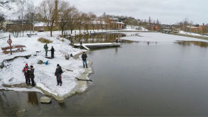 Ihmisiä kalastamassa rannalla. Maassa on hento lumipeite, vesi on sulaa. Taustalla on taloja.