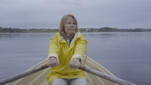 Eija soutelemassa soutuveneellä keltainen sadetakki päällä