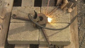 En stor metallmutter svetsas så att den får tre armar.