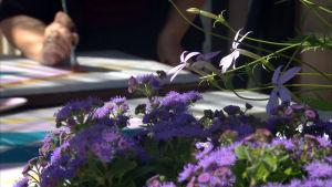 Blommor i förgrunden och händer som målar i bakgrunden