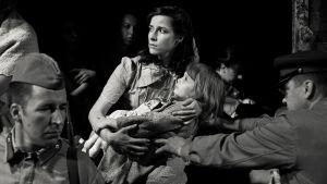 Nainen pitelee lasta sylissään elokuvassa Ristituulessa