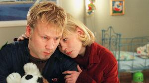 Jarkko Sarjanne eli Söder ja Pirjo Moilanen eli Laura lähikuvassa murheellisina. Lauralla on hänen kätensä Söderin olkapäällä ja käsivarrella.