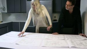 Mies ja nainen tutkivat rakennuspiirrustuksia