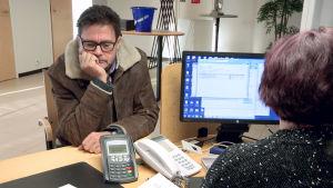 Mies istuu toimistossa pöydän ääressä