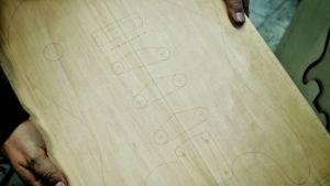 Tervaleppälankku, johon piirretty laserpolttimella kitaran ääriviivat.