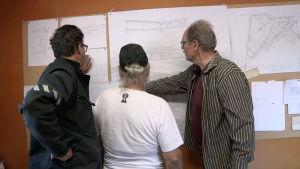 Arkkitehti, rakennuttaja ja timpuri tutkivat piirrustuksia