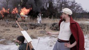 Samurai maalaa talon palaessa taustalla. Kuva elokuvasta Samurai Rauni Reposaarelainen