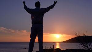Mies katsoo auringonlaskua merenrannalla