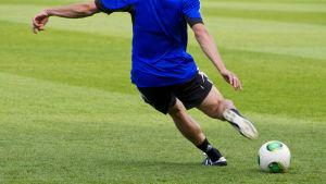 Jalkapalloilija potkaisee palloa Helsingin olympiastadionilla.
