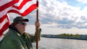 Ohjaaja Michael Moore etsii ratkaisuja Yhdysvaltain ongelmiin. Hän vierailee dokumentissaan mm. Suomessa.