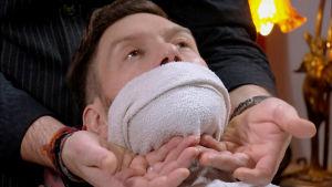 En man har en fuktig handduk på ansiktet och halsen.