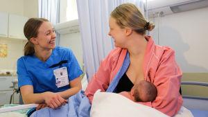 Mamma med bebis vid bröstet. Till höger om henne sitter en barnmorska.