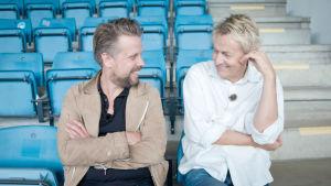 Filip Hammar och Lars Lerin sitter på en fotbollsläktare.