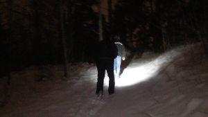 Två personer går i en mörk skog.