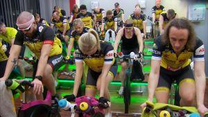 En grupp cyklister tränar på spinningcyklar inomhus.