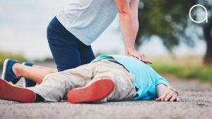 Nainen elvyttää maassa makaavaa miestä.