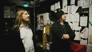 Två män, Ville Karttunen och Aki Tykki, står i ett trångt utrymme och tittar på papperslappar  med olika bands låtar i spelordning upphängda på väggarna.