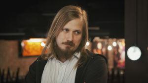 Man med skägg och långt hår.