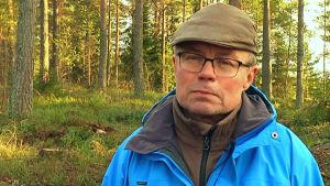porträttbild av man i skog.