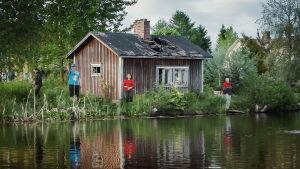 Några personer står och fiskar vid en å, i bakgrunden ett ruckel med hål i taket.