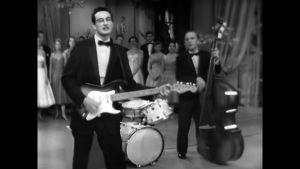 Buddy Holly soittamassa kitaraa.