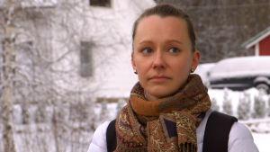 Belinda Andersson står och väntar på bussen, närbild av ansiktet.