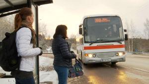 Belinda Andersson står på busshållplatsen och väntar på bussen. Bussen kommer.