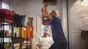 Mies vaihtaa lamppua, nainen katsoo taustalla.