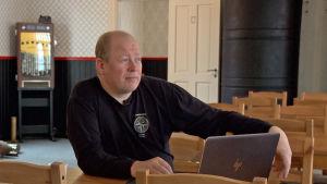 Man sitter vid ett bord i ett före detta soldathem på Rysskär.