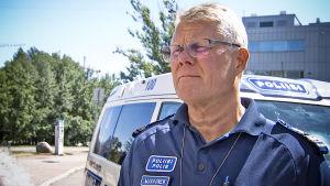 Överkommissarie Jorma Makkonen vid en polisbil