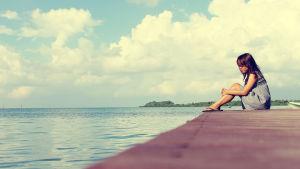 en flicka sitter ensam på en brygga
