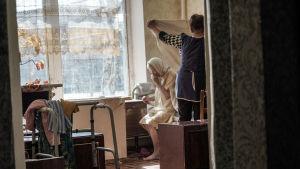 En sköterska byter lakan åt en åldring i åldringshemmet i Ukraina.