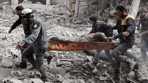 Män bär en bår med en sårad person i östra Ghouta, Syrien.