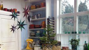 Julstjärnor i papper hänger från taket i Strömsös kök.