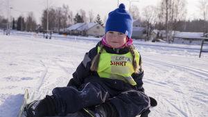 Lotta Koro har skidor på och sitter på marken.